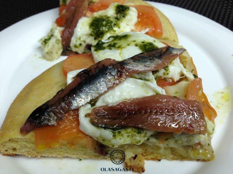 Focaccia with Olasagasti Anchovy fillets, mozzarella, tomato and pesto sauce.