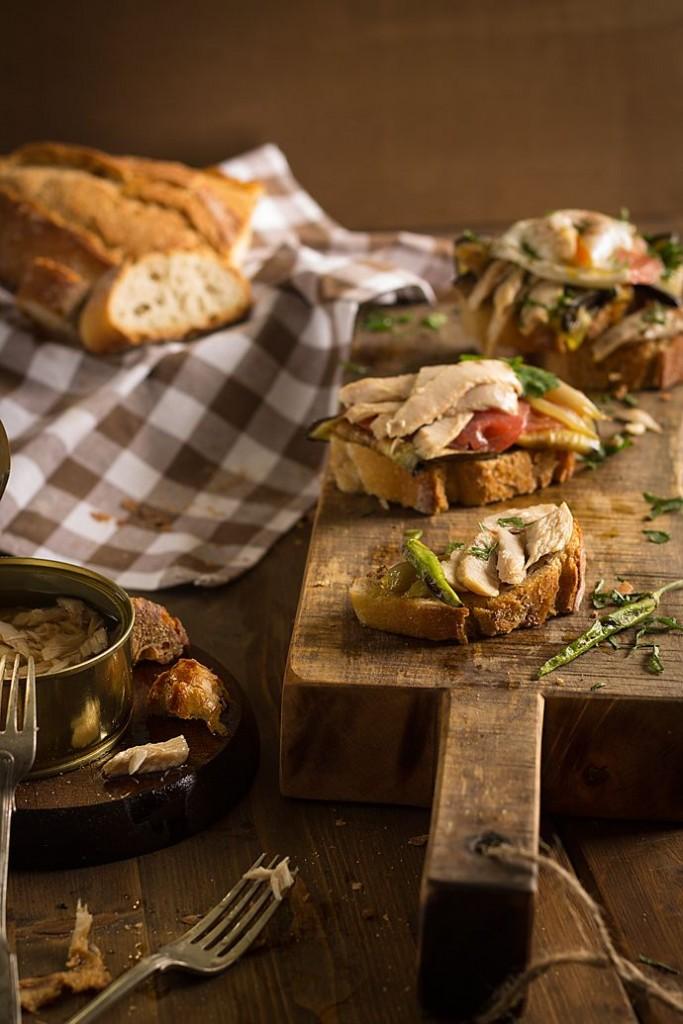 Bruschetta de ventresca de bonito del norte con verduras y huevo sobre tabla de madera