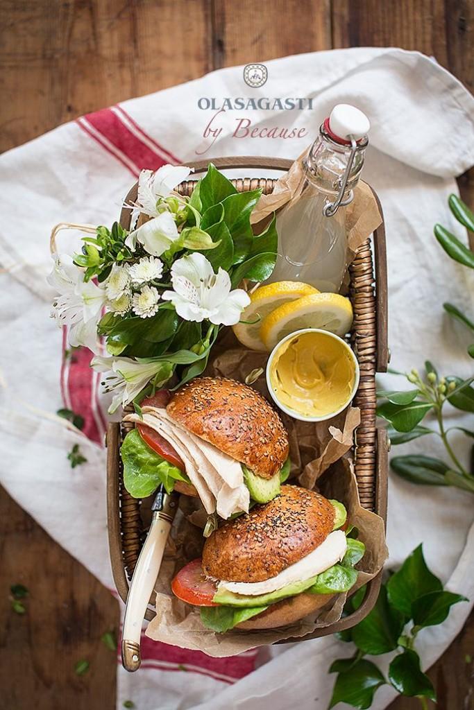cesta con sandwich vegetal con ventresca, una botella con limonada y flores
