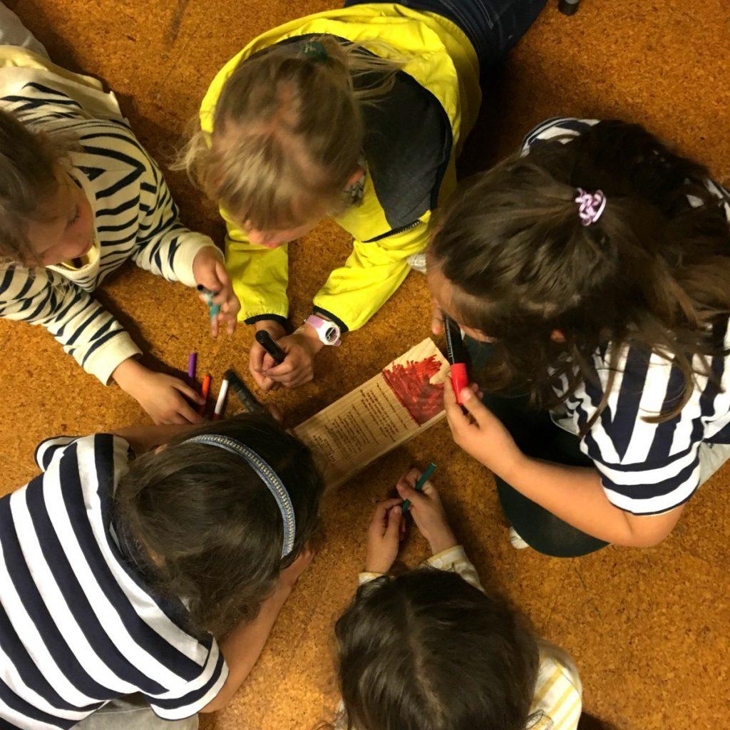 Niños pintando barcos de madera en proyecto para mantener un mar vivo y limpio