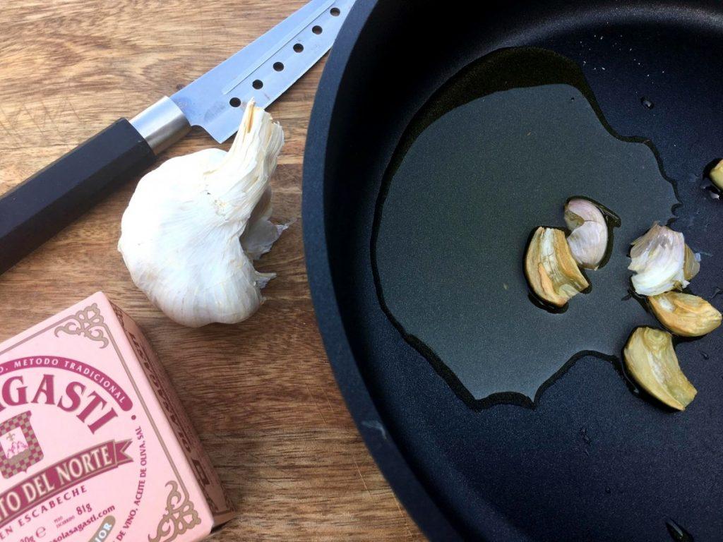 Ajo en una sartén con aceite para la coliflor salteada con bonito del norte