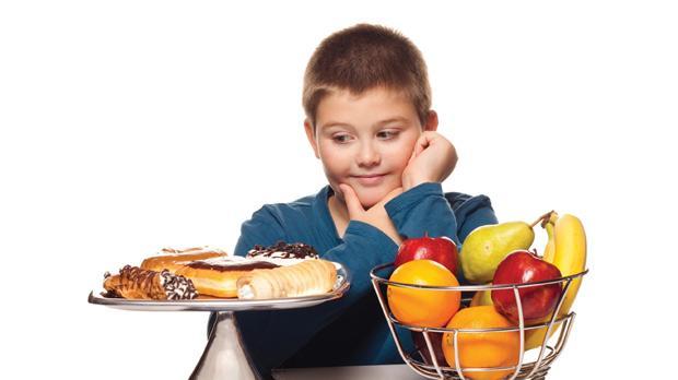 Niño debatiéndose entre bollería industrial y fruta fresca. Comer con conciencia sería la segunda opción.