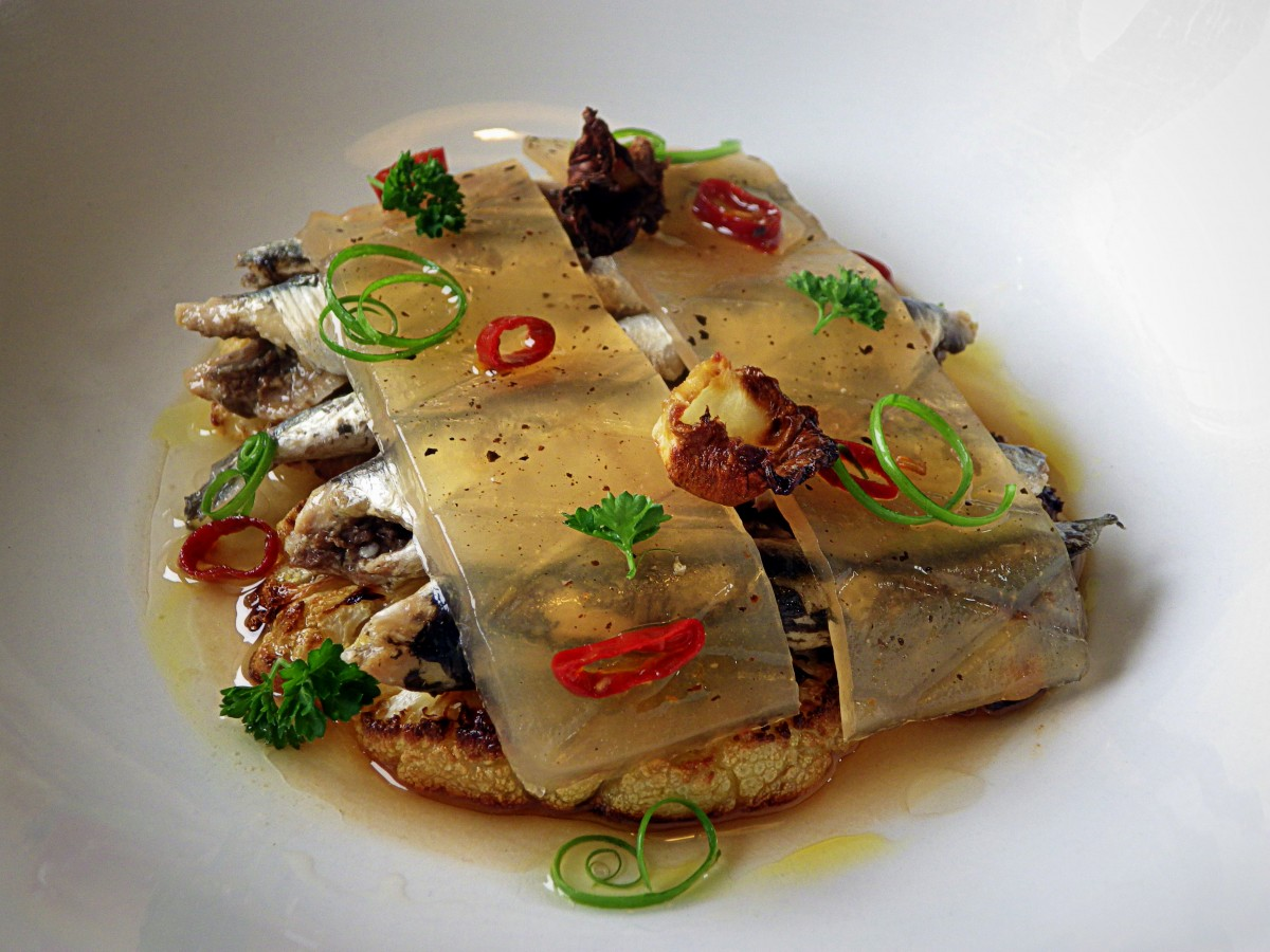El mar condimentado en un plato con anchoas a la donostiarra Olasagasti, coliflor y gelatina de tomate