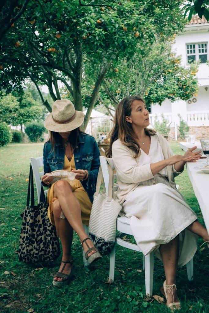 Dos mujeres en el jardín de Federica & Co con flores y bastidores.