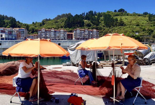 Tres rederas de Ondarroa cosiendo en el puerto.
